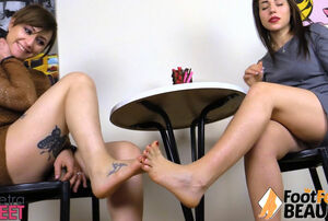 2 femmes have fun footsies under the..